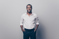Portrait of glad confident intelligent attractive african man wearing white shirt with rolled-up sleeves holding hands in pockets isolated on gray background