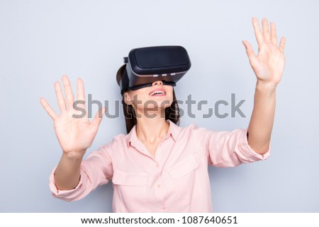 Portrait of glad, excited girl getting experiencewith VR googles  , touching virtual wall with two palms, gesturing with hands isolated on grey background