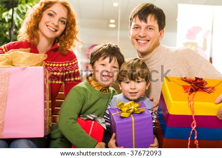 Portrait of glad family members with lot of gifts sitting in supermarket after shopping