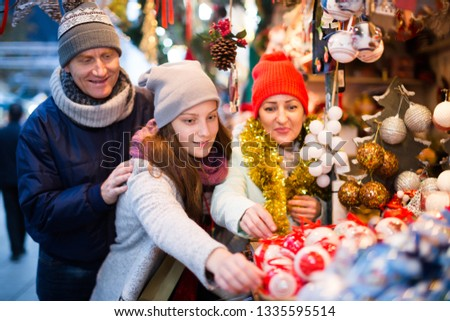 Portrait of glad family with teenager girl at  Christmas fair