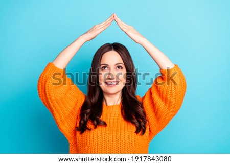Portrait of glad nice lady look hands make house figure above head toothy smile isolated on blue color background Foto stock ©