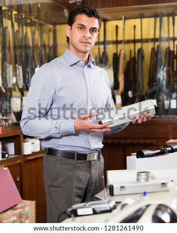 Portrait of glad salesman proposing hunting equipments in specialized shop