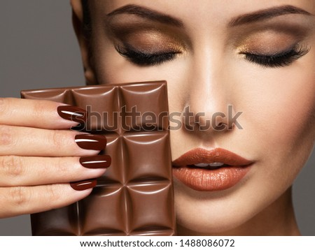Portrait of glamour Beautiful woman with brown nails holds bar of chocolate