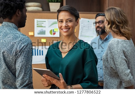 Portrait of glamour business woman looking at camera with colleagues working in background. Successful fashion businesswoman standing with her staff in background at modern office.