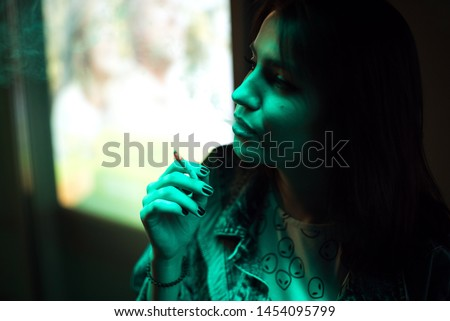 Portrait of glamour gorgeous brunette woman smoking cigarette in neon color light. She's wearing an alien shirt.