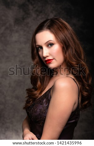 Portrait of glamourous young woman wearing elegant vintage evening dress/gown, against a classic studio backdrop.