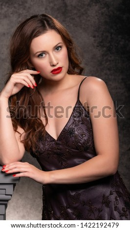 Portrait of glamourous young woman wearing elegant vintage evening dress/gown, set against a classic studio backdrop.