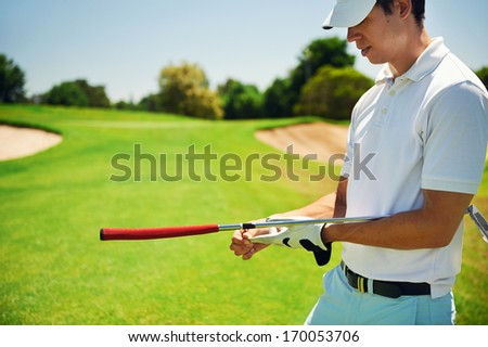 Portrait of golfer removing golf glove while holding putter on green
