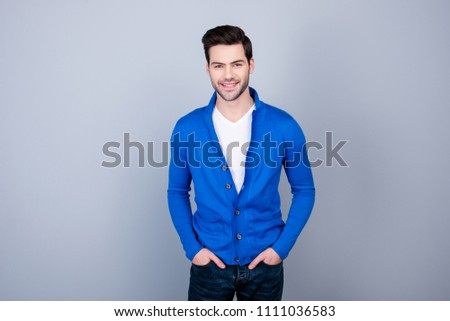 Portrait of good guy in blue cardigan holding his hands in pocket, looking at camera, standing over grey background