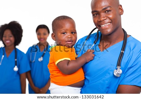 portrait of good looking african american male pediatric doctor with little boy and female nurses on background
