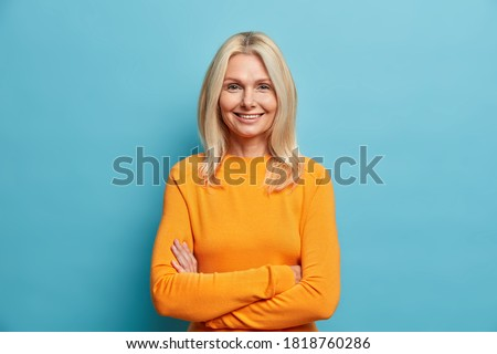 Portrait of good looking blonde woman stands self assured against blue studio background smiles gently and keeps arms folded glad to meet old friend. People age beauty sincere emotions concept