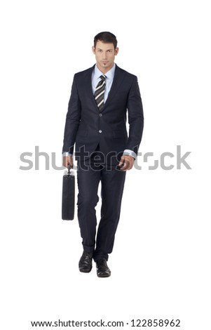 Portrait of good looking businessman holding briefcase while walking on a white surface