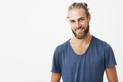 Portrait of good-looking nordic unshaven man with fashionable hairdo posing for magazine article about young successful business people.