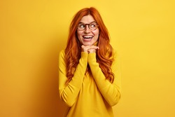 Portrait of good looking redhead European woman smiles broadly keeps hands under chin looks aside gladfully wears casual jumper expresses happiness isolated over yellow background. Monochrome shot