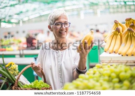 Portrait of good-looking senior woman buys bananas at the market