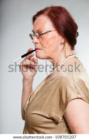 Portrait of good looking senior woman wearing glasses with expressive face showing emotions. Smoking a cigarette. Acting young. Studio shot isolated on grey background. - stock photo