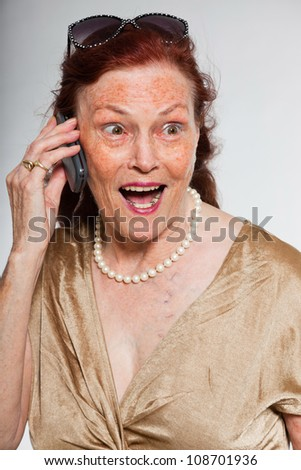 Portrait of good looking senior woman with expressive face showing emotions. Calling with cell phone. Acting young. Studio shot isolated on grey background.