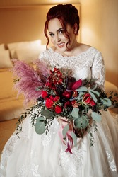 Portrait of gorgeous adorable bride holding big wedding bouquet. Beautiful pretty woman look at the camera, smiling, excited about marriage. Attractive adult lady wearing stylish bridal white dress