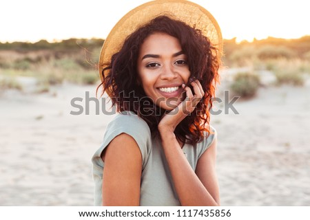Portrait of gorgeous african american woman 20s in summer straw hat laughing and looking at you while walking on sand at seaside