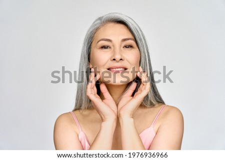 Portrait of gorgeous beautiful middle aged mature asian woman, senior older 50 year lady looking at camera touching her face isolated on white. Ads of lifting anti wrinkle skin care, spa.