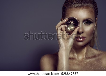 Portrait of gorgeous chic blond woman with wet hair, glittering artistic make-up and bronze skin holding a big shining gem in front of her eye. Jewellery concept. Studio shot. Close up. Copy-space