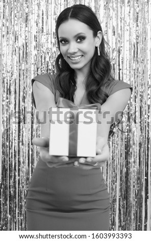 Portrait of gorgeous elegant hispanic brunette woman in luxurious red dress holds a gift box and posing on silver shiny tinsel background. Studio shot.