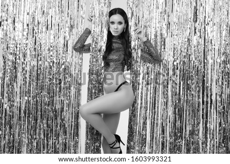 Portrait of gorgeous elegant hispanic brunette woman with perfect body in luxurious silver sequin top posing on shiny tinsel background. Studio shot.