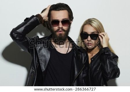 Portrait of gorgeous fashion beautiful couple in black clothes wearing trendy glasses and posing over white background together. Hipster boy and girl. Bearded young man and blonde in sunglasses