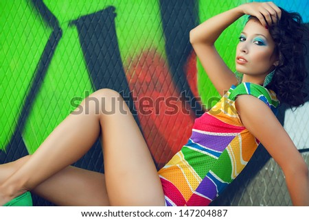 Portrait of gorgeous fashion model with arty make-up of green, blue colors sitting, touching hair over graffiti background. Vintage turquoise earrings. Colorful trendy clothes. Disco style. Copy-space