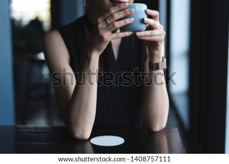 Portrait of gorgeous female drinking tea or coffee and looking with smile out of the coffee shop window while enjoying her leisure time, nice business woman lunch in modern cafe during her work break #1408757111