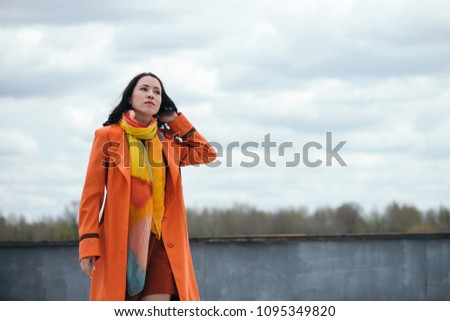 Portrait of gorgeous girl with black curly hair in orange cloak and varicolored bright scarf on background of cloudy sky. Girl look in distance. Dreaming gaze of beautiful female eyes. #1095349820