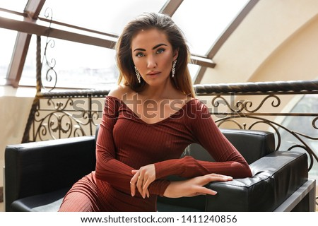 Portrait of gorgeous lady in fashionable dress with long sleeves, open shoulder. Sitting on the black sofa near the big window. Volume long hairstyle, makeup, accessories. Amazing blue eyes, big lips. #1411240856