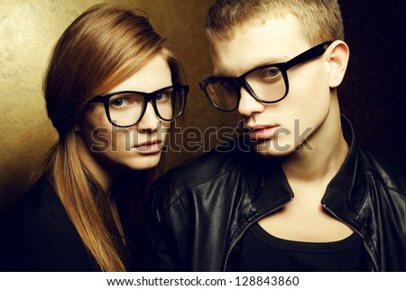 Portrait of gorgeous red-haired fashion twins in black clothes wearing trendy glasses and posing over golden background together. Perfect hair. Natural make-up. Perfect skin. Studio shot.