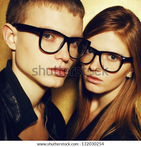 Portrait of gorgeous red-haired fashion twins in black clothes wearing trendy glasses and posing over golden background together. Perfect hair. Natural make-up. Perfect skin. Vogue style. Close up