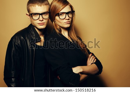 Portrait of gorgeous red-haired fashion twins in black clothes wearing trendy glasses and posing over beige background together. Perfect hair. Natural make-up. Perfect skin. Studio shot