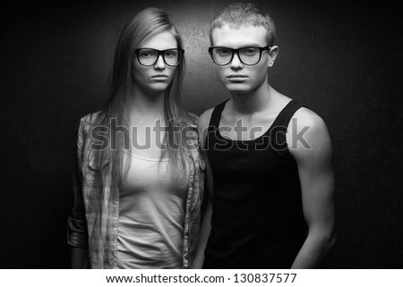 Portrait of gorgeous red-haired fashion twins in casual shirts wearing trendy glasses and posing over golden background together. Black and white (monochrome) studio shot.
