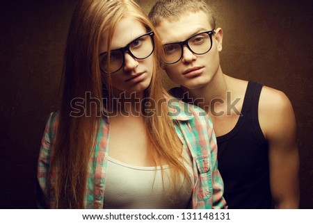 Portrait of gorgeous red-haired (ginger) fashion twins in casual shirts wearing trendy glasses and posing over golden background together. Hipster style. Studio shot.