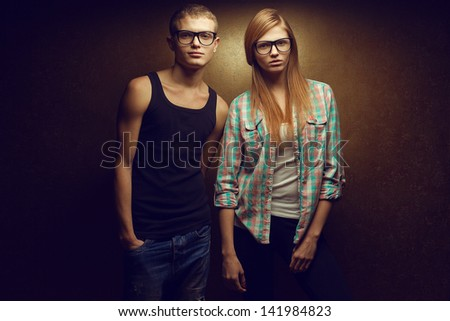 Portrait of gorgeous red-haired (ginger) fashion twins in casual shirts wearing trendy glasses and posing over golden background together. Hipster style. Copy-space. Studio shot
