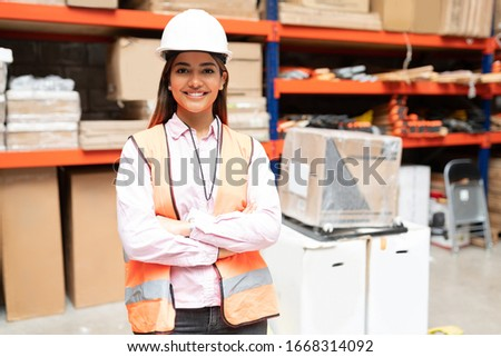 Portrait of gorgeous smiling employee standing with arms crossed against rack at warehouse Stock foto ©