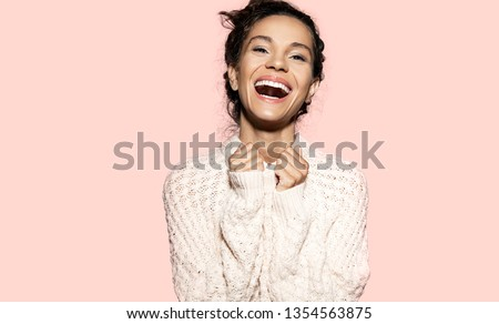 Portrait of gorgeous smiling woman wearing snow white knitted sweater. Cute girl looking at camera with happiness. Happy model posing in studio. Isolated on pink background #1354563875