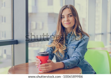 Portrait of gorgeous smiling young beautiful excited cheerful with curly hair hairstyle woman drinking takeaway coffee from disposable cup. She is having a break at work. #1006589986