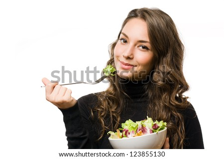 Portrait of gorgeous young brunette eating juicy fresh salad.