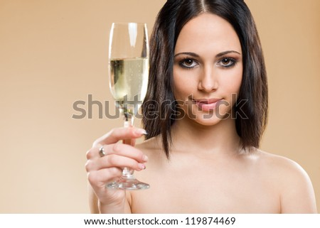 Portrait of gorgeous young brunette with glass of champagne on golden background.