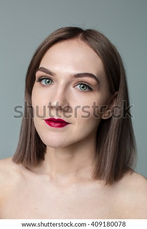 Portrait of gorgeous young caucasian attractive sexy woman with business makeup. Red lips and green eyes #409180078