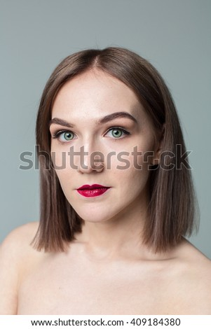 Portrait of gorgeous young caucasian attractive sexy woman with business makeup. Red lips and green eyes #409184380