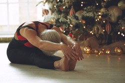 Portrait of gorgeous young woman practicing yoga indoors at Christmas time. Beautiful girl practice in the class. High quality photo.