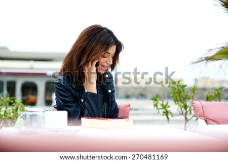 Portrait of gorgeous young woman talking on mobile phone while sitting in restaurant terrace, brunette woman having cell phone conversation with someone smiling, woman relaxing on exterior terrace