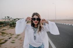 Portrait of graceful stylish girl in black sunglasses and white blouse having fun next to highway in summer. Charming long-haired young woman wearing vintage tunic walking down the road in evening.