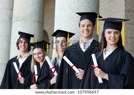 Portrait of graduates posing in single line with columns in background