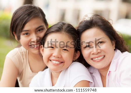 Portrait of granddaughters with grandmother smiling at camera outdoors